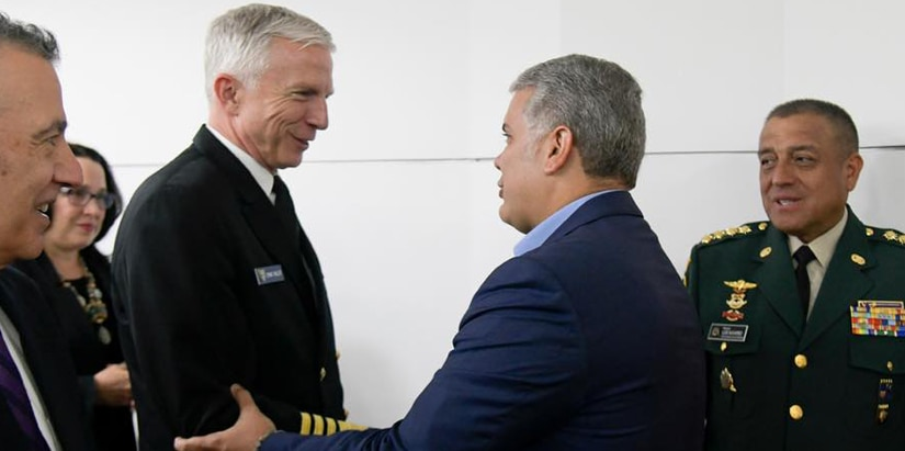 Navy admiral shakes hands with a man dressed in a suit.