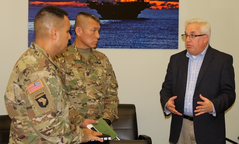 Army Sgt. Majs. Marco Torres, left, and Fu Pi, center, listen as DLA Troop Support Industrial Hardware Director of Supplier Operations Gary Shifton explains IH's role in tracking Army ground forces readiness drivers Jan. 10, 2020, in Philadelphia.