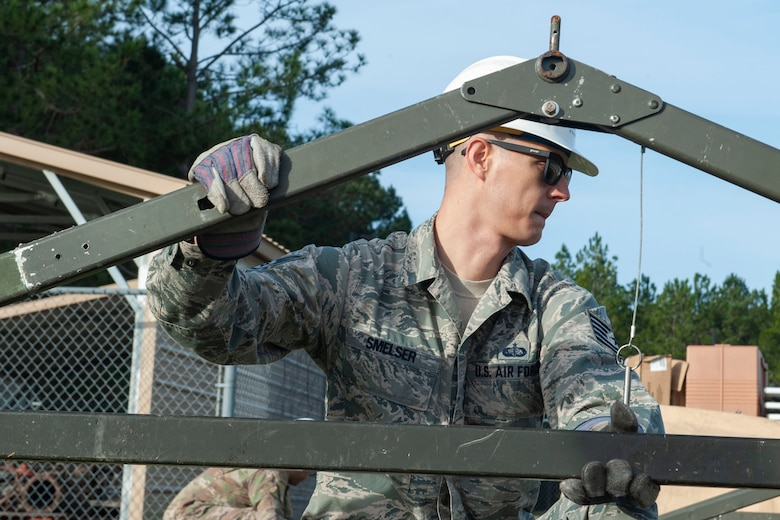 Photo of an Airman holding tent structure parts
