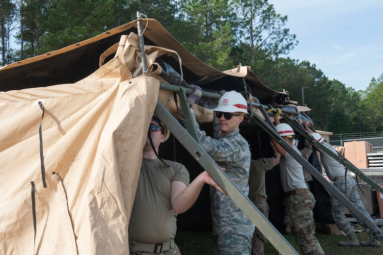 Photo of Airmen putting up a tent