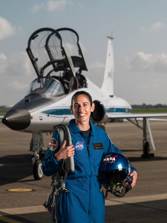 A female astronaut wearing a blue flight suit and NASA-logoed helmet poses in front of a T-38 Talon trainer airplane.