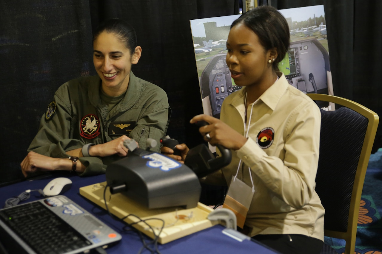 A pilot in flight suit sits beside a teenager who's using the joystick of a computer simulator. Both are watching a screen.