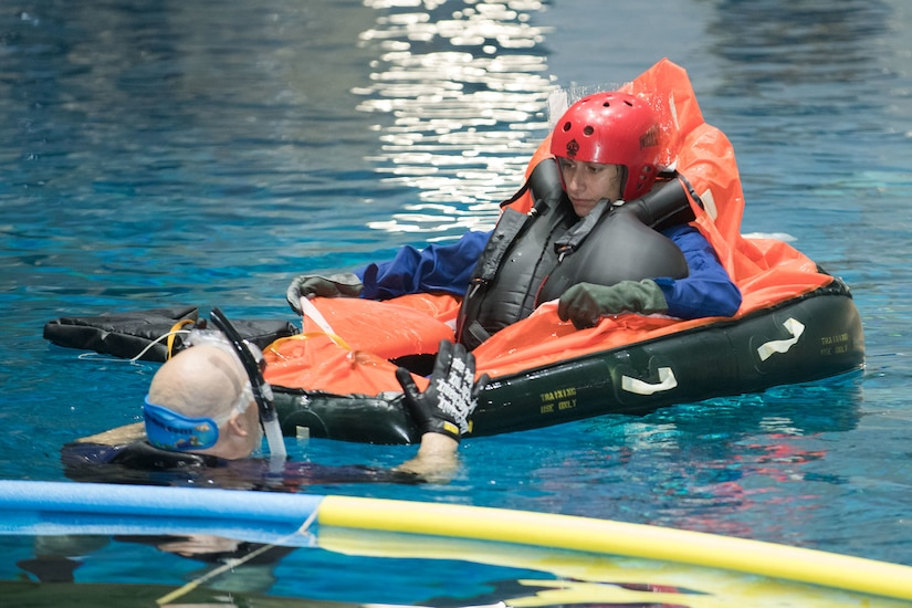 A woman wearing a large blow-up vest and helmet sits in an inflatable in a pool while taking instruction from a man in the water in a diving suit with snorkel.