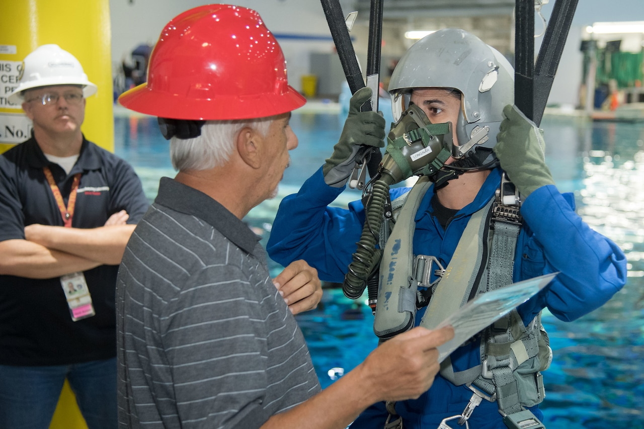 A trainee wearing a mask, helmet and what appears to be parachute cables listens to a man wearing a red hardhat. A pool is in the background.