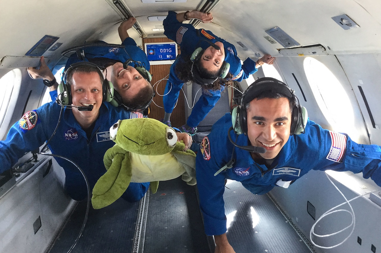 Four astronaut candidates in flight suits smile at the camera as they float in a reduced gravity environment on an airplane.