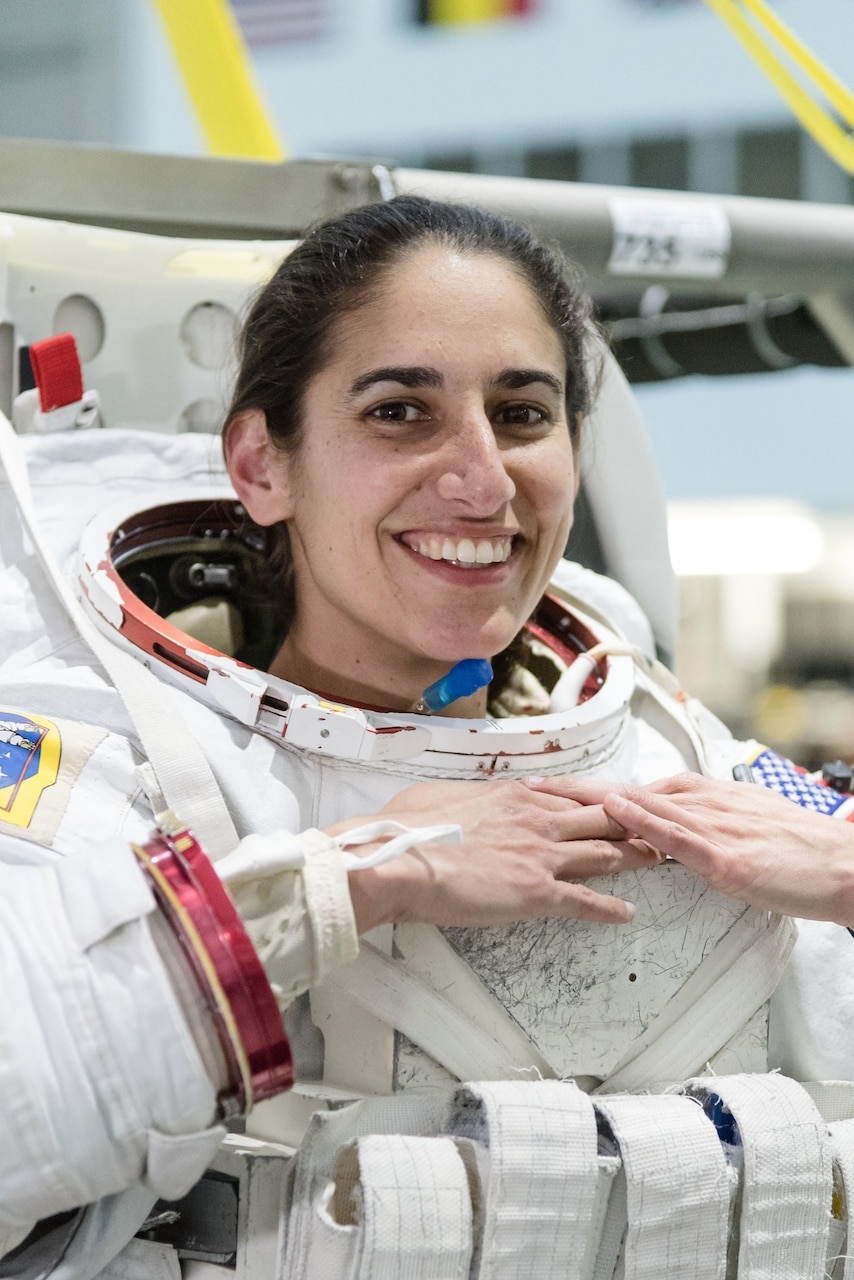 An astronaut candidate wearing a spacesuit without the helmet smiles.