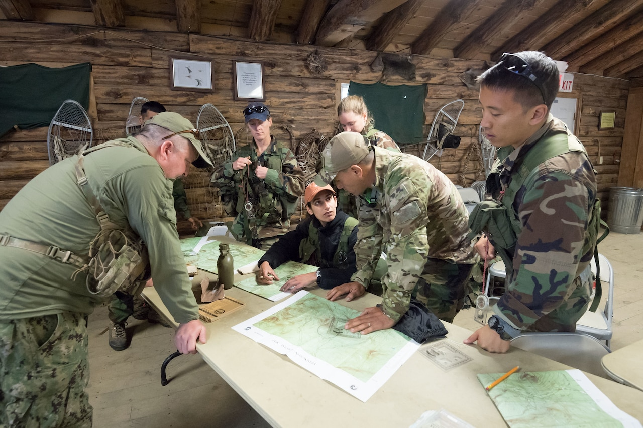 Seven people in military camouflage sit and stand around a table looking at maps in what appears to be a wooden log cabin.