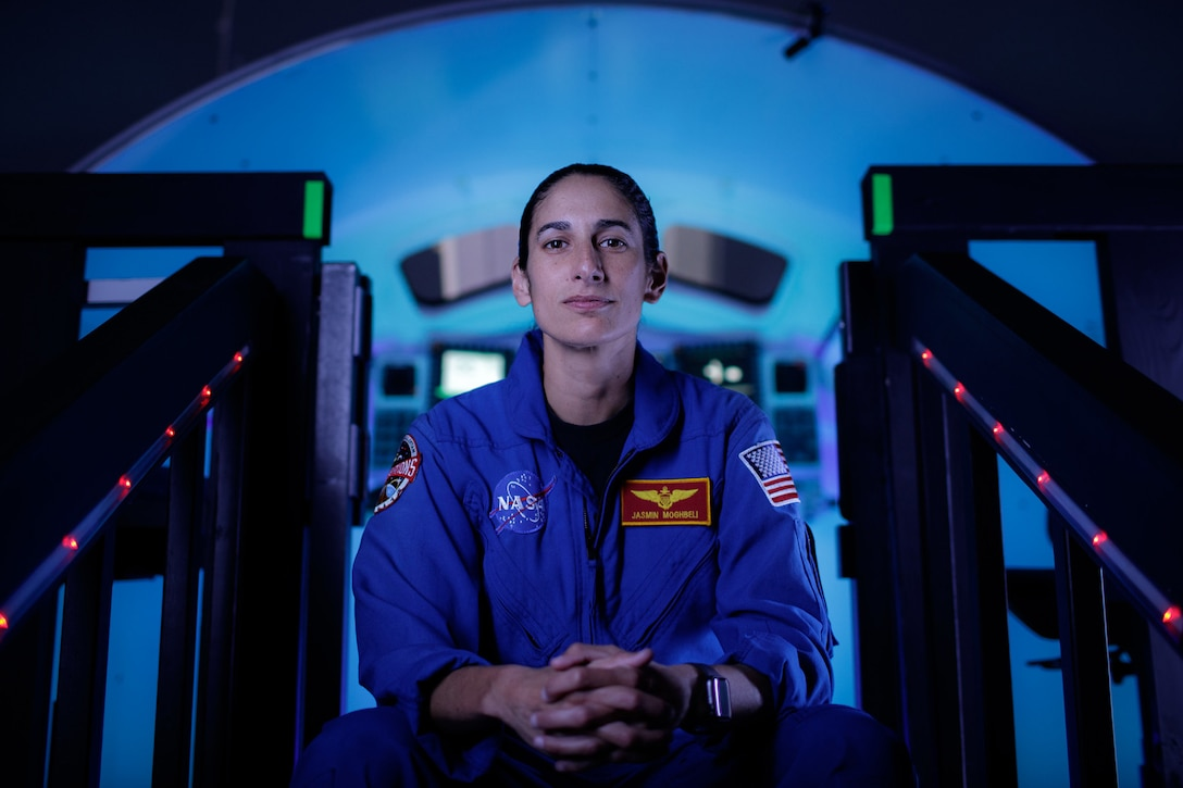 An astronaut in a blue flight suit sits on darkened steps, clasping her hands. A blue light illuminates a control room in the background.