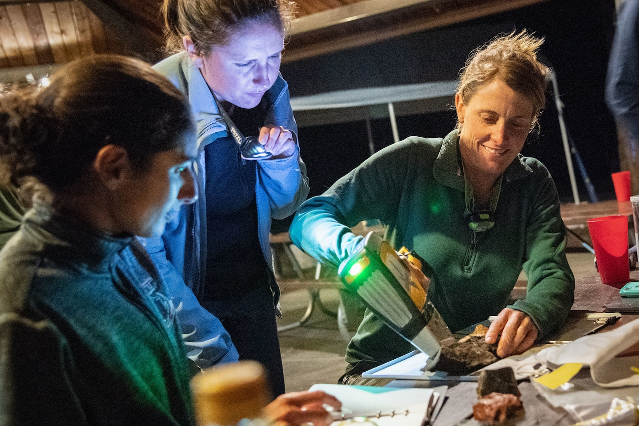 Three women huddle around a rock as they sit at an outdoor picnic table at night. One holds a flashlight while a second scans a rock on the table with a device.
