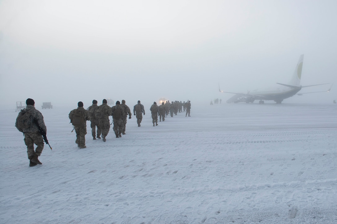 A line of soldiers begin boarding a plane on a snowy runway.