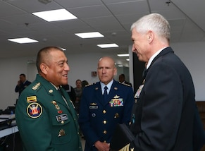 Colombian Chief of Defense Maj. Gen. Luis Navarro and U.S. Navy Adm. Craig S. Faller greet each other.