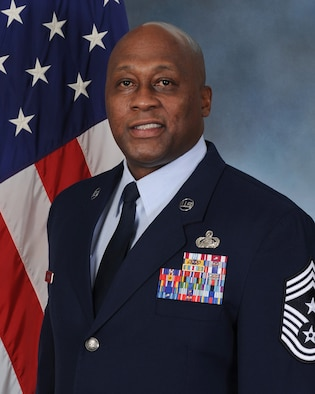 Image is Chief Master Sergeant Ronald Harper's official biography photo. He is wearing a blue service dress coat. The US flag is behind his shoulder.