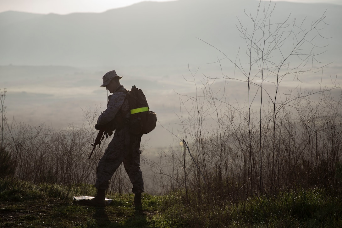 A service member with a pack on his back stands on a foggy hill holding a rifle.