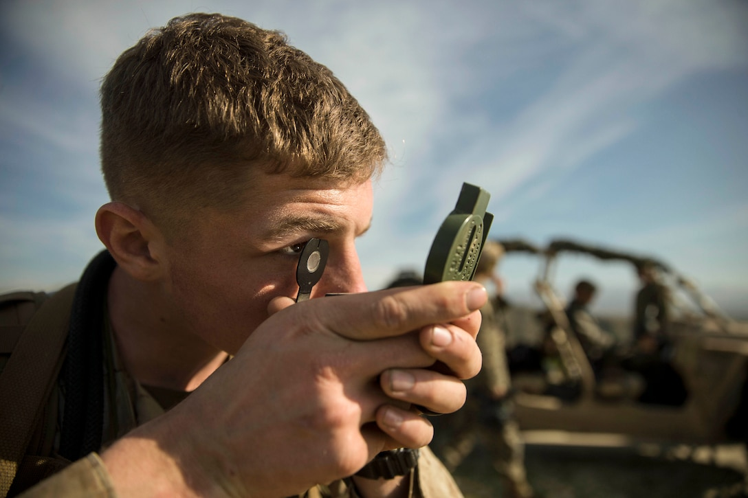 A Marine holds a compass up to their eyes.