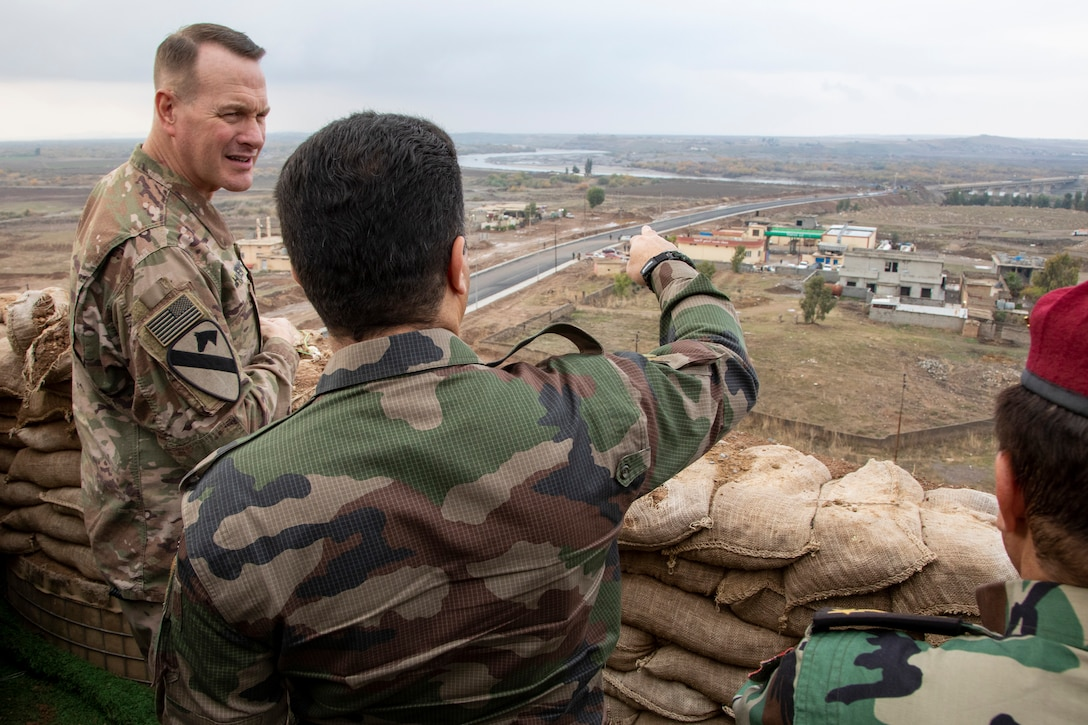 Two men in camouflage uniforms stand near a sandbag wall looking out over a town.