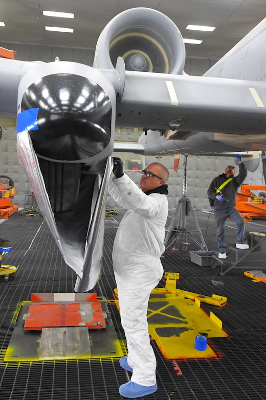 A technician is using a placing a cover on part of the wing of an A-10 aircraft located inside a lighted depaint facility.