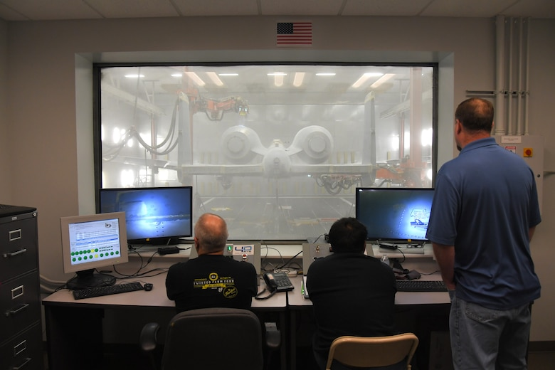 Three technicians around a desk monitor computers and look through a window in front of them where and A-10 aircraft is being depainted by two robots flanking the aircraft.
