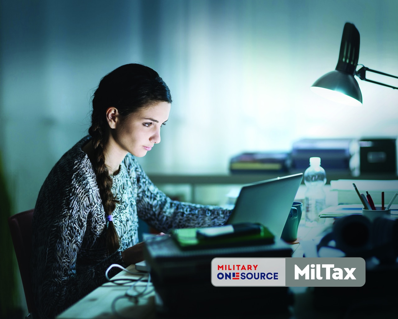 A person looks at a computer screen, The image has a Military Onesource MilTax logo superimposed on it.