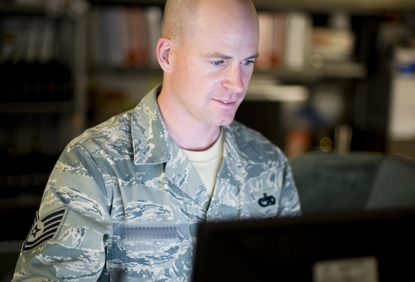 An Air Force technical sergeant looks at a computer screen, Name tape is digitally altered to protect his identity.