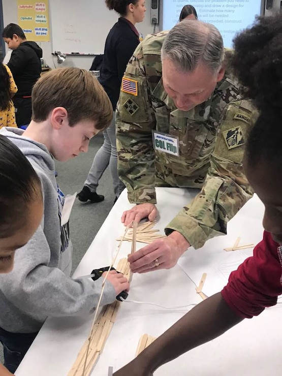 USACE Middle East District Commander COL Philip Secrist assist members of Team echo during the bridge build competition at STARBASE Academy, in Winchester, Va., by pointing out comparative strengths of various shapes.
