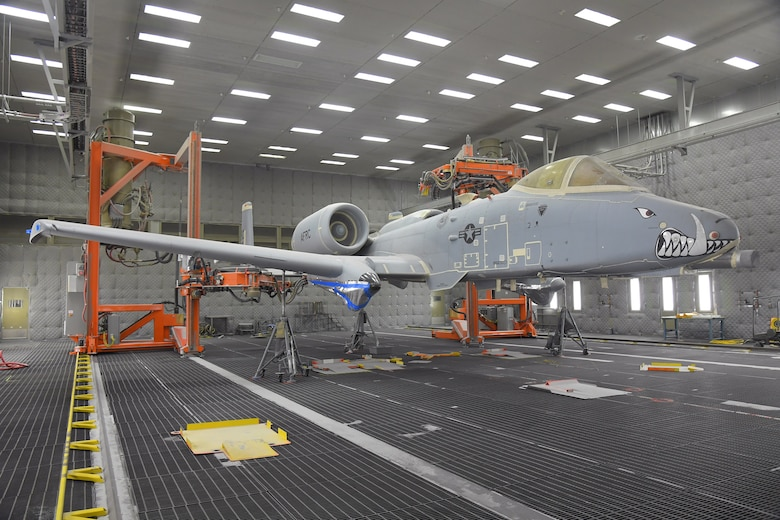 An A-10 aircraft sits on jacks in a lighted depaint facility with two orange depainting robots flanking it in the background.