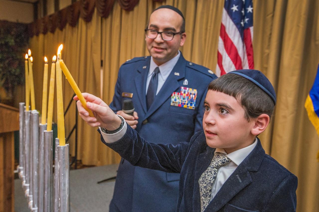 A chaplain observes as a child lights a candle on a menorah.