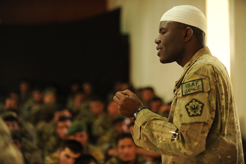 A chaplain in military uniform addresses a room full of military personnel.