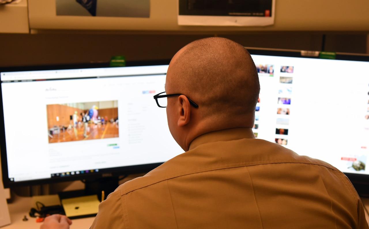 A man looks at computer screens.