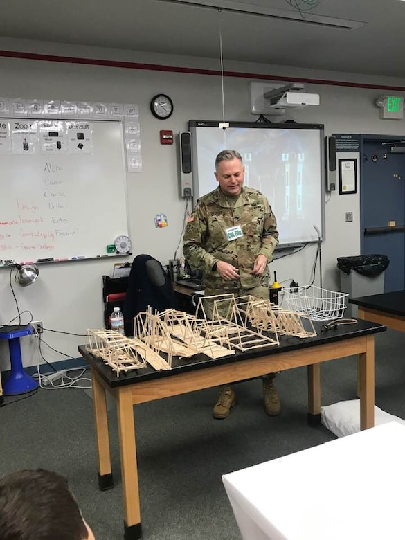 TAM Commander COL Philip Secrist at the start of the testing phase of the bridge build activity, looking over the various submissions.