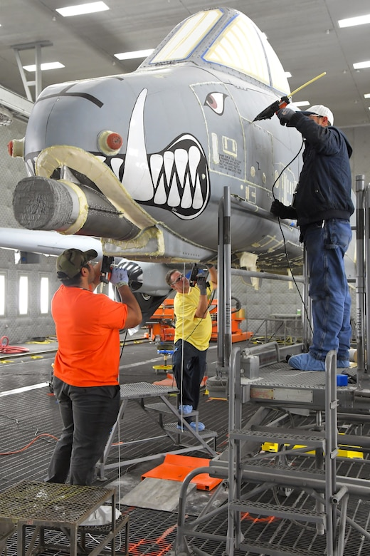 Three technicians work on the nose of an A-10 aircraft in a lighted depaint facility.