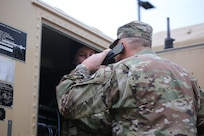 Command Sgt. Major Christopher Kepner, senior enlisted advisor to the chief, National Guard Bureau, helps a soldier check communication equipment before the start of a Command Post Exercise at Camp Murray, Wash., Jan. 10, 2020.