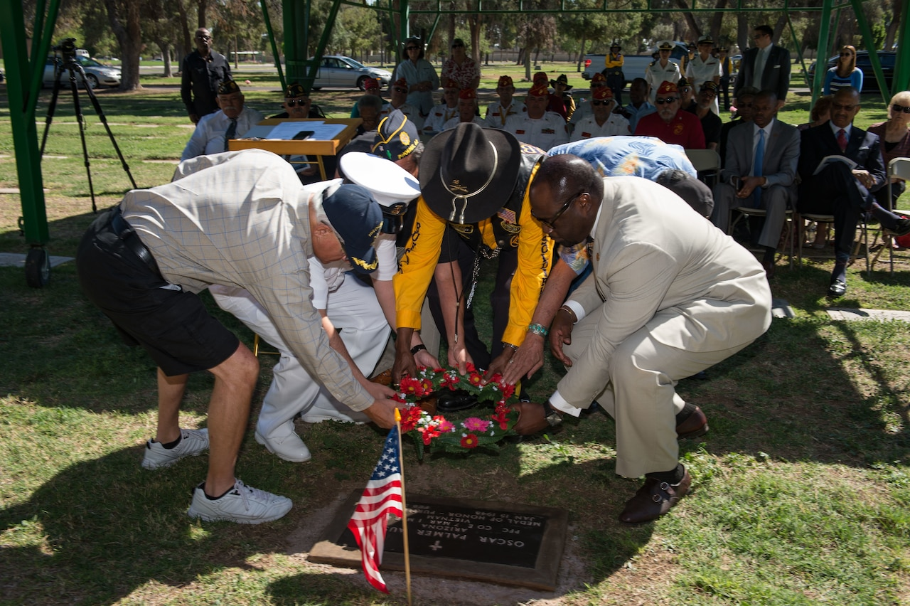 Five older gentlemen lay a wreath at a gravestone as several veterans seated in the background look on.