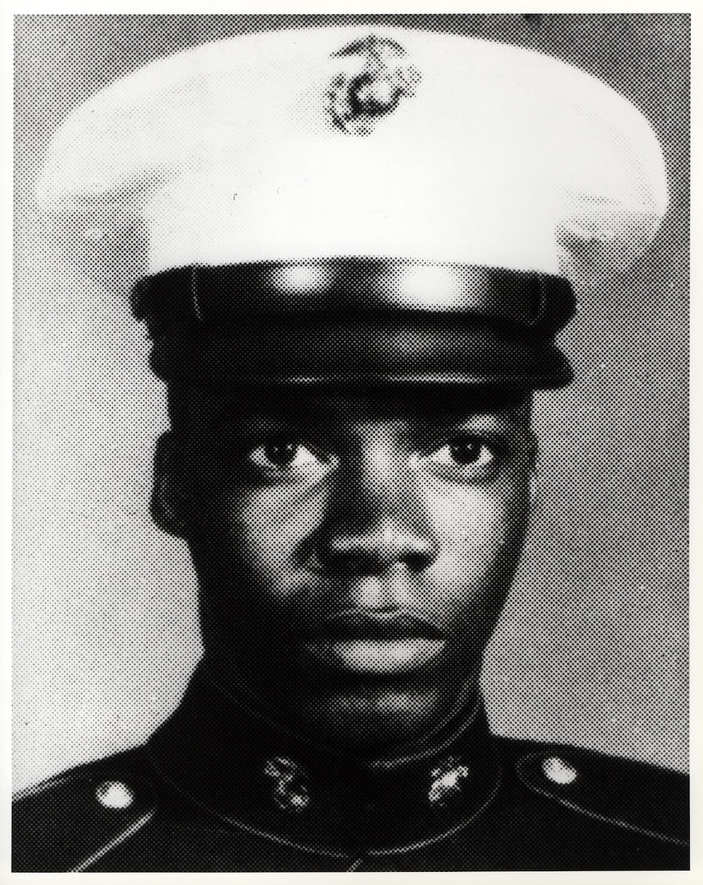 A young Marine wearing a dress cap.