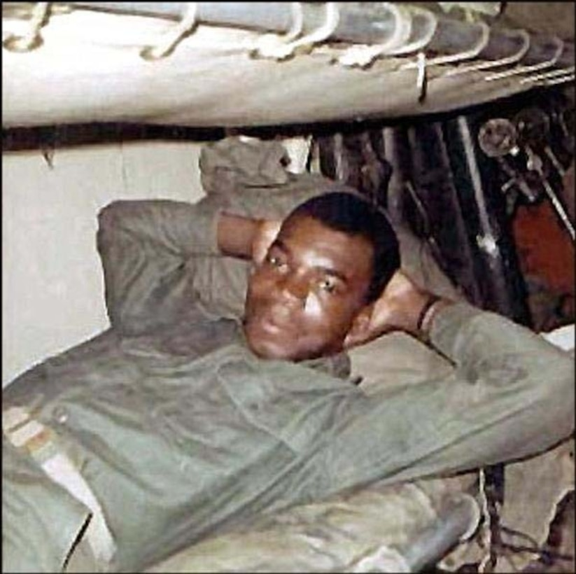 A young Marine in utility uniform relaxes in a bunk with his hands behind his head.