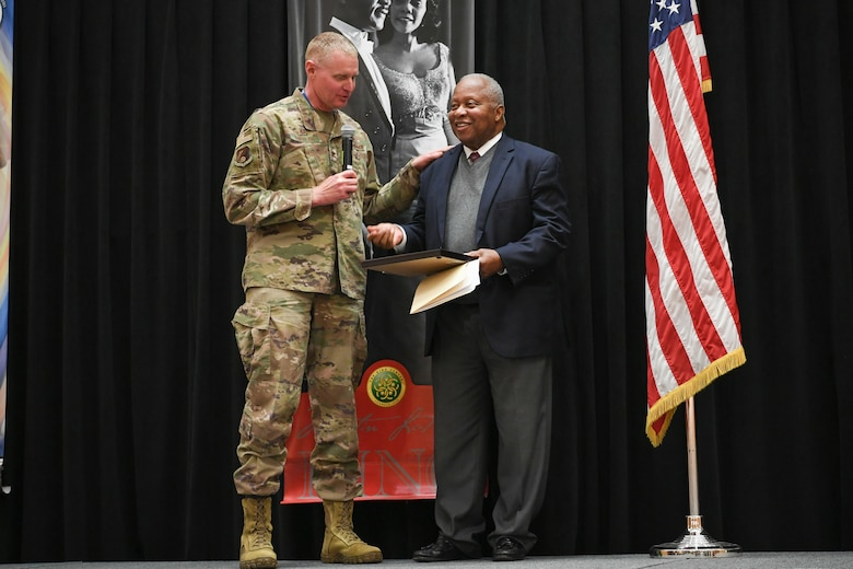 Col. Jon Eberlan, 75th Air Base Wing commander, presents Dr. Ronald Gerald Coleman with a gift at the Martin Luther King, Jr. Commemoration Luncheon Jan. 16, 2020, at Hill Air Force Base, Utah. Coleman, a retired University of Utah professor of African American history, was the special guest speaker at the event. (U.S. Air Force photo by Cynthia Griggs)