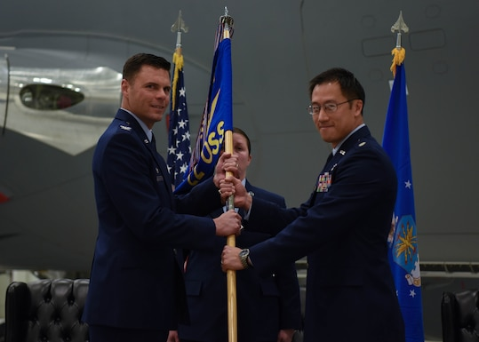 Col. Thad Middleton, 22nd Operations Group commander, passes the 22nd Operations Support Squadron guidon to Lt. Col. Kenneth Louie, the incoming 22nd OSS commander, during a change of command ceremony Jan. 16, 2020, at McConnell Air Force Base, Kansas. Louie accepted the reins of responsibility, authority and accountability when after accepting the 22nd OSS guidon from Middleton. (U.S. Air Force photo by Airman 1st Class Marc A. Garcia)