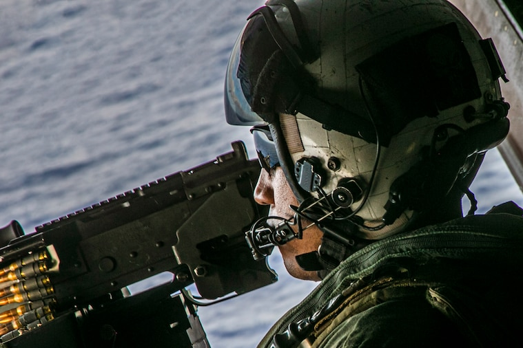 A Marine wears a helmet and sunglasses while in an aircraft over the sea.