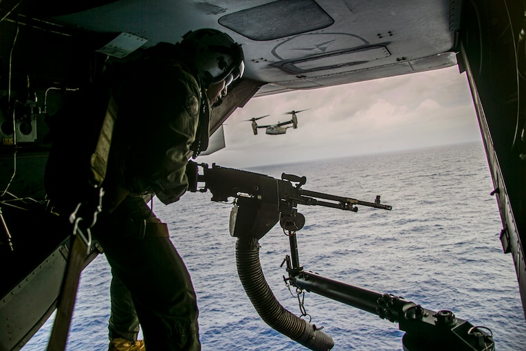 A Marine fires a weapon while over the sea as an aircraft passes in the background.