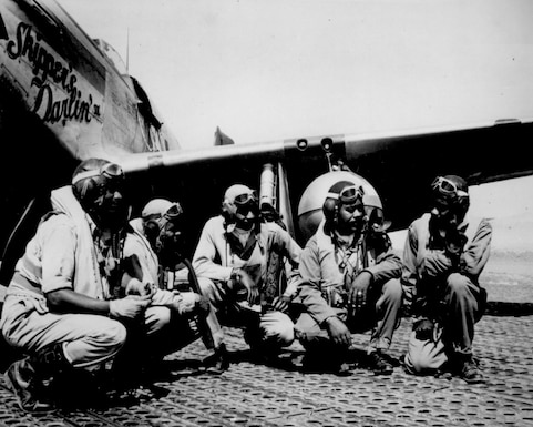 Fliers of a P-51 Mustang Group of the 15th Air Force in Italy talk in the shadow of one off the Mustangs they fly, August 1944. Left to right, Lt. Dempsey W. Morgan Jr., Lt. Carroll S. Woods, Lt. Robert H. Nelson Jr., Capt. Andrew D. Turner, and Lt. Clarence P. Lester.