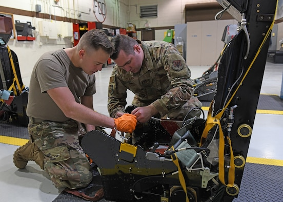 Airman 1st Class Robert Dumbeck (left), 9th Maintenance Squadron aircrew egress systems journeyman, and Tech. Sgt. Cody Clark 9th MXS aircrew egress systems craftsman, inspect an egress seat D-ring before installing a D-ring guard, Jan. 16, 2020 at Beale Air Force Base, California. When a pilot pulls the D-ring, it fires an initiator that sends gas pressure to explosives. Each of these explosives fire at different items like the lap belt, inertia reel, and foot retractors. (U.S. Air Force photo by Airman 1st Class Luis A. Ruiz-Vazquez)