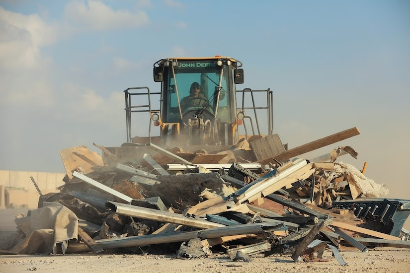 A soldier uses a bulldozer to push a pile of metal construction debris.