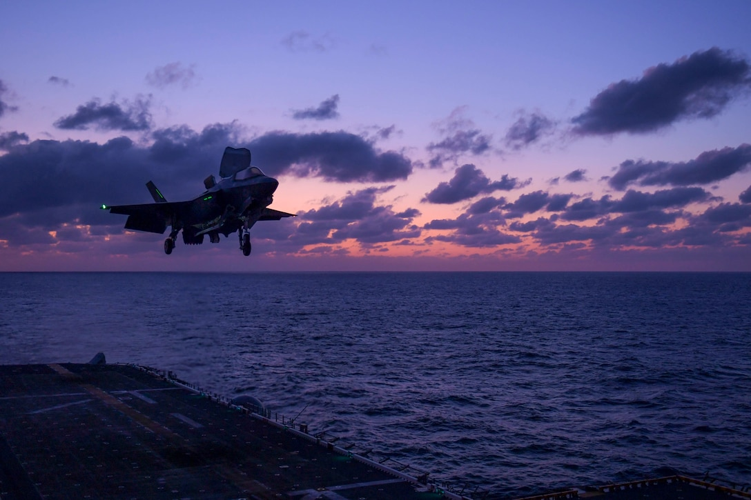 A military aircraft prepares to land on a ship.