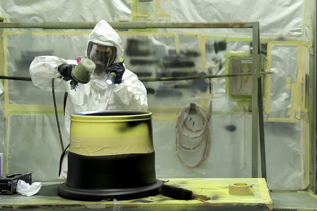 An airman wears protective gear while spray painting a  landing gear wheel.