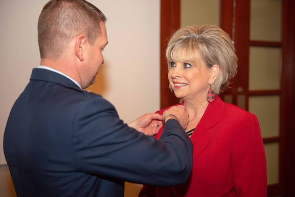 Col. Mark Baran, 22nd Air Refueling Wing vice commander, pins a commander badge on Kathy Bond, 22nd ARW honorary commander, at the honorary commander assumption of command Dec. 4, 2019, at McConnell Air Force Base, Kansas. Bond was previously the honorary commander of the 22nd Operation Support Squadron before moving up to the wing level. (U.S. Air Force photo by Staff Sergeant Chris Thornbury)