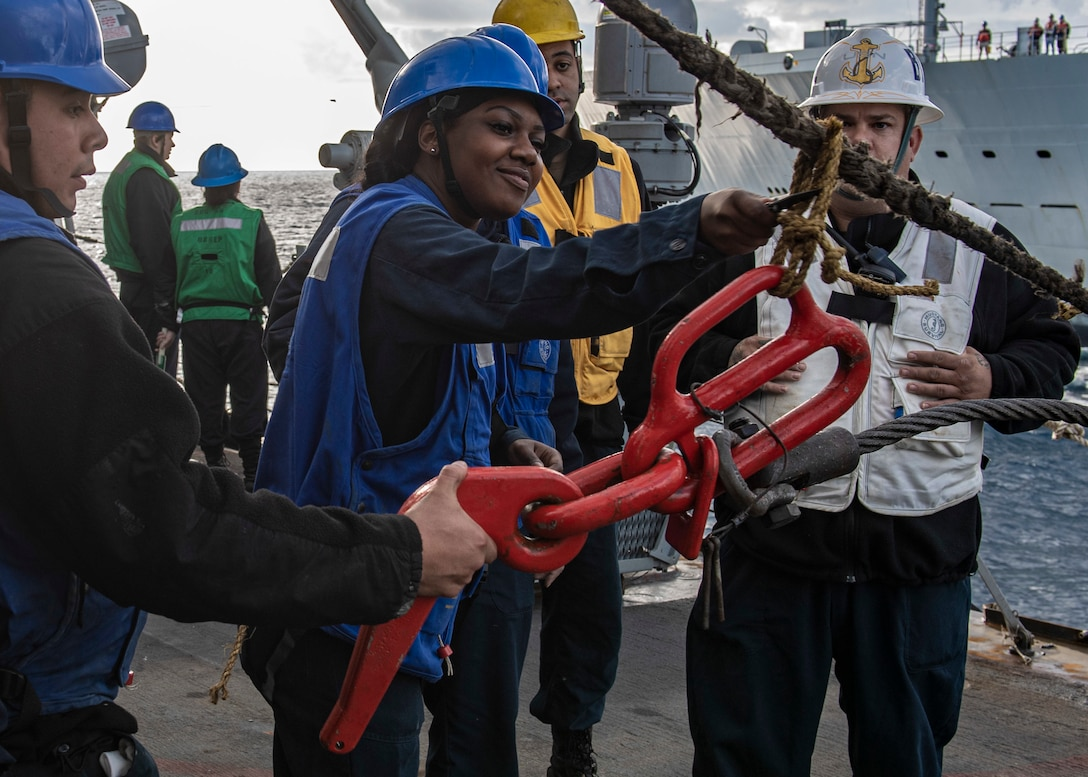 A sailor cuts a rope while others surround.