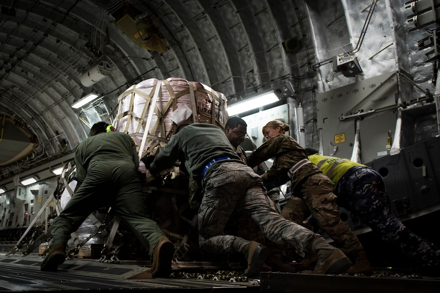 Airmen and RAAF Airmen push fire suppressant on to aircraft.