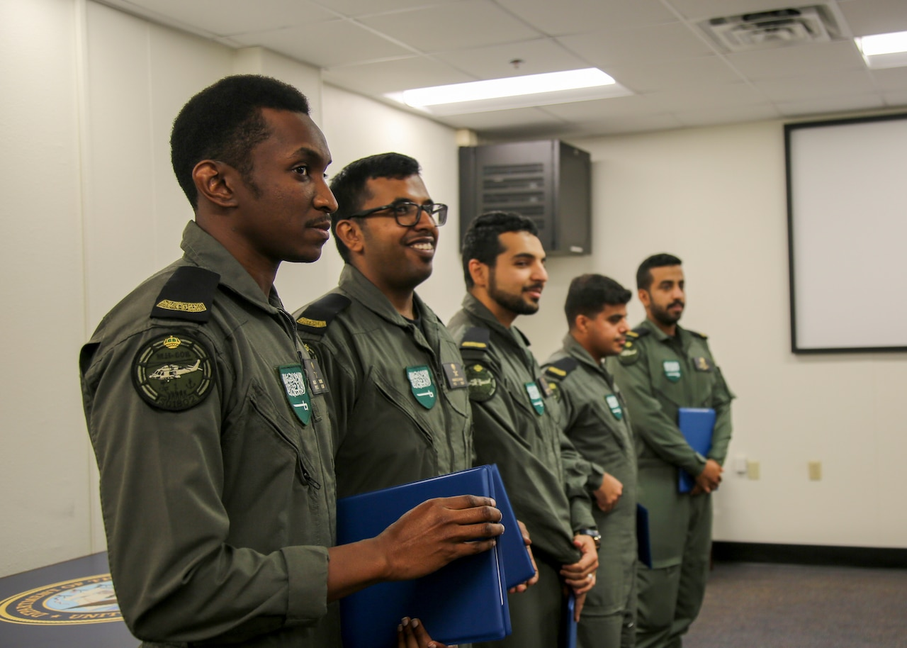 Five military personnel stand in line, each holds a blue folder.