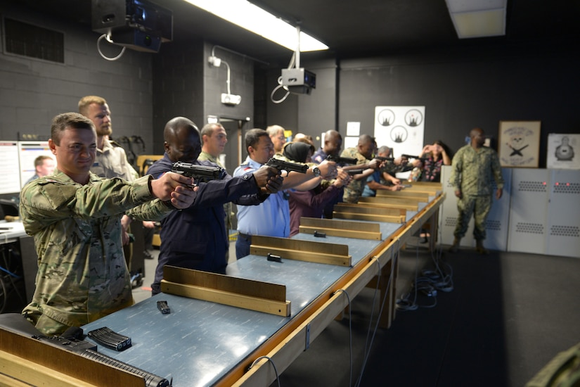 A line of military personnel stand behind a long table and fire hand guns.