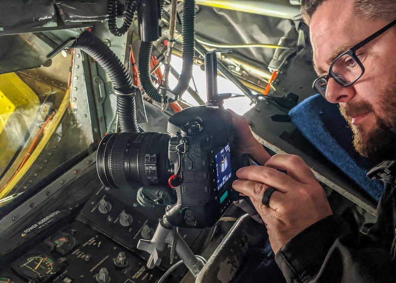 Ethan Wagner, 412th Test Wing aerial photographer, prepares his camera inside a KC-135 Stratotanker at Edwards Air Force Base, Jan. 17. The 412th Test Wing will send a KC-135 and three F-16 Fighting Falcons to conduct a flyover for the NFC championship game at Levi's Stadium in Santa Clara, California, on Jan. 19. (Air Force photo by Crosby Shaterian)