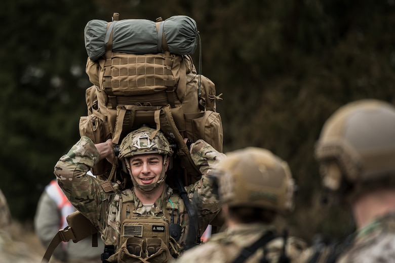 U.S. Air Force Staff Sgt. Mark Melchiori, 435th Security Forces Squadron contingency response fire-team leader, hoists a rucksack over his head after stepping off a bus for exercise Frozen Defender in Grostenquin, France, Jan. 14, 2020. Frozen Defender tests the squadron's capabilities in a contested environment under harsh conditions. The 435th SFS Defenders must be physically prepared to carry more than 70 lbs of equipment into these environments. (U.S. Air Force photo by Staff Sgt. Devin Boyer)